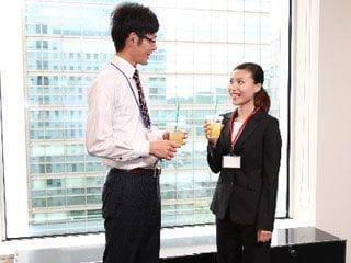 窓際でジュースを飲みながら談笑しているスーツ男女