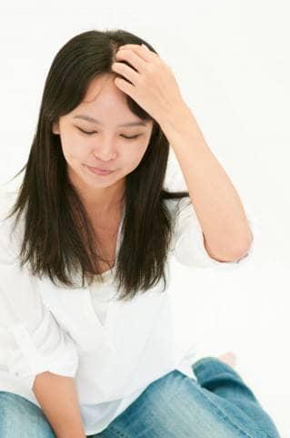髪の分け目を抑えるジーンズ女性
