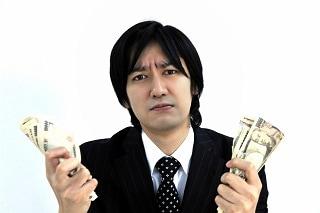 お金を両手で持っているスーツ男性