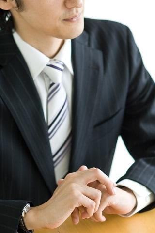 テーブルで手を組むスーツ男性