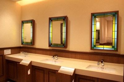 洗面台。さわやかなミントブルーとグリーンのステンドグラスに縁取られた鏡が並びます。