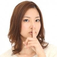 口に指を当てる女性