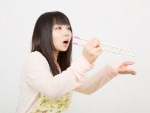 菜箸を持つ女性