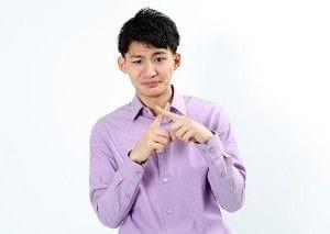 指でバツをつくる男性