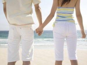 浜辺で手を握るカップル