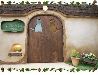 てまりのおうち入口扉の窓。2匹の猫がお出迎えしてくれます