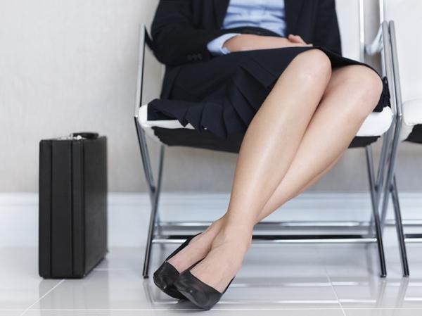 足首をクロスさせて座る女性