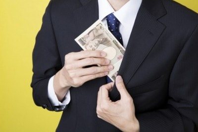 スーツのポケットからお金を出す男性