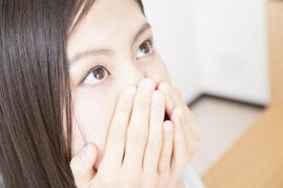 口を隠す女性