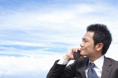 携帯電話で話すスーツの男性