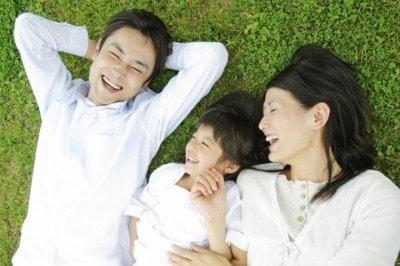 芝生に寝転ぶ夫婦と子ども
