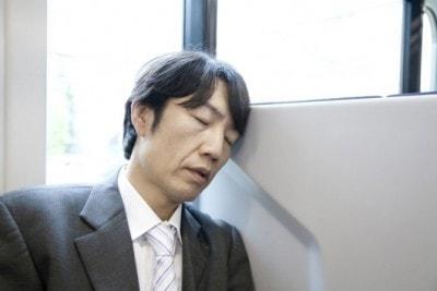 電車でうたた寝をする男性