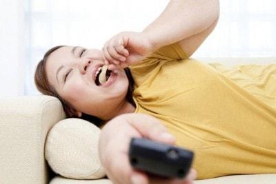 寝転がってお菓子を食べる女性