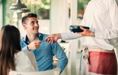 レストランで支払いをする男性